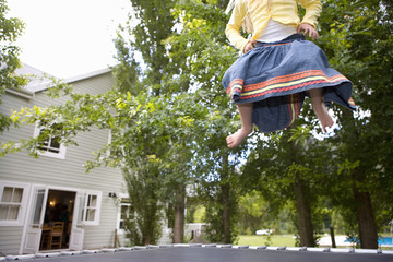 Girl (9-11) playing on trampoline in garden, low section