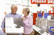 Mature couple shopping, man holding computer in box, smiling at each other