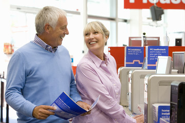 Mature couple shopping for computer, smiling at each other