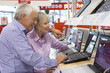 Mature couple shopping for laptop computer, smiling, side view