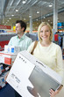 Young couple shopping, woman with computer in box, man with printer in box, smiling, portrait