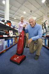 Mature couple shopping for hoover, smiling, portrait, low angle view