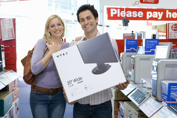 Young couple shopping, with computer in box, smiling, portrait