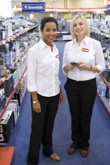 Young saleswoman with colleague in shop, smiling, portrait