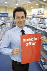 Young salesman with 'special offer' sign in electronics aisle, smiling, porttrait