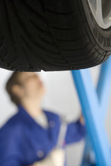Female mechanic with wrench by elevated car, focus on tyre