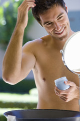 Bare chested man doing hair in mirror, smiling