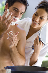 Woman in bathrobe helping bare chested man apply shaving cream