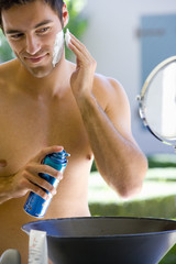 Bare chested man applying shaving cream in vanity mirror, smiling
