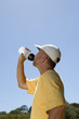 Man in exercise clothes drinking from bottle, low angle view