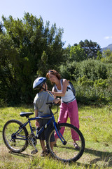 Boy (6-8) with bicycle, mother adjusting son's helmet