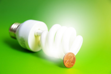light bulb with a penny, (energy costs), on green