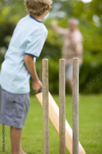 Boy (10-12) playing cricket with father, low angle view