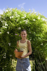 Girl (10-12) with flower pot by hedge, smiling, portrait