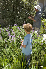Father and son (8-10) gardening, boy with hose, rear view