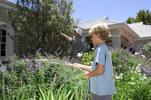 Father and son (8-10) gardening, boy with hose, side view