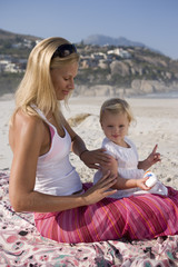 Mother applying sunscreen to baby girl (12-15 months) on beach, side view