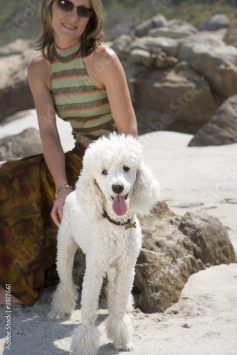 Woman on rock with dog on beach, smiling