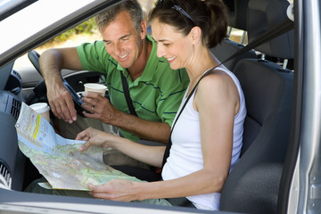 Mature couple looking at map in car, man with disposable cup, smiling