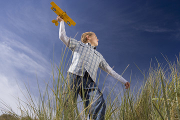 Boy (7-9 years) holding up toy airplane, running in long grass, low angle view