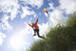 Girl (7-9 years) flying kite outdoors, low angle view