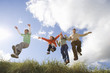Family of four jumping on grass outdoors, low angle view