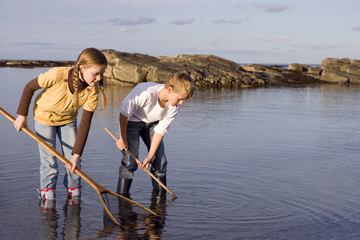Boy and girl (7-9 years) holding fishing nets in lake