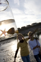 Boy and girl (7-9 years) standing by jar containing starfish, smiling, portrait