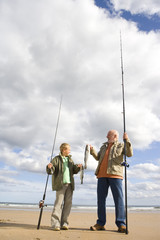 Grandfather and grandson (7-9) on beach with fishing rods and fish, smiling at each other, low angle view