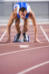 Male athlete in starting blocks, portrait, low angle view