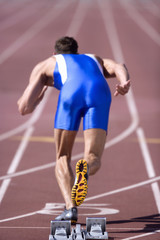 Male athlete by starting blocks, rear view
