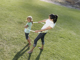 Mother and daughter (6-8) playing with hula hoop on grass in park, smiling, side view, elevated view
