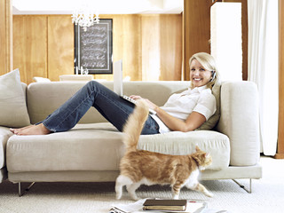 Woman with headphones and laptop relaxing on sofa at home, smiling, portrait, cat walking on carpet