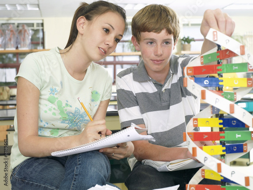 Teenage boy and girl (15-17) sitting at desk in classroom, studying DNA model