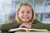 Girl (9-11) reading textbook at desk in classroom, smiling, close-up, front view, portrait