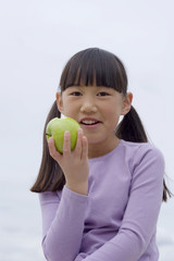 Girl (9-11) eating green apple, smiling, front view, close-up, portrait