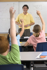 Male teacher standing beside whiteboard in classroom, children (9-11) with hands raised