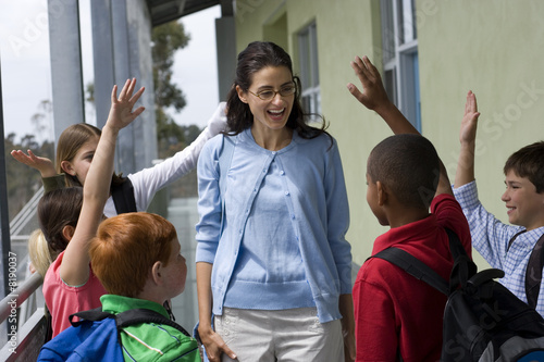 Female teacher talking to class outside school, children (9-12) with hands raised