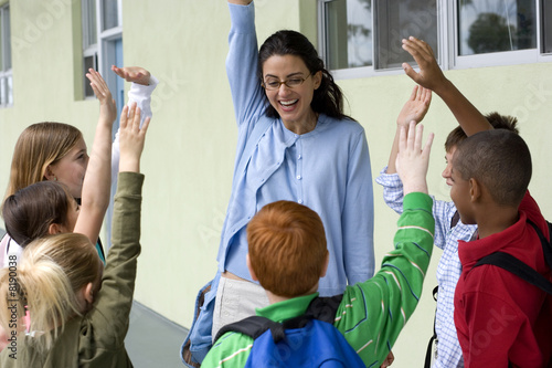 Female teacher talking to children (9-12) outside school, hands raised