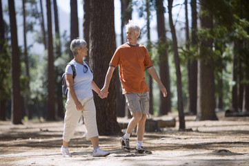 Active senior couple walking in wood, holding hands, smiling