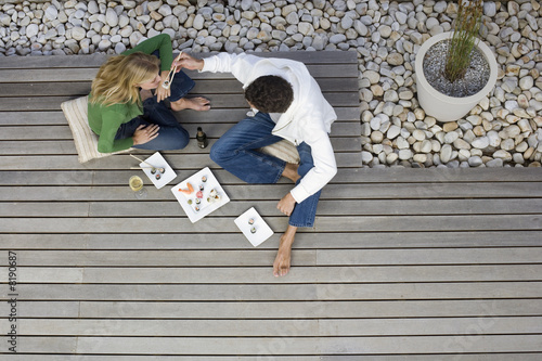 Couple sitting on patio decking, eating sushi with chopsticks, overhead view