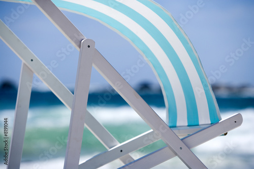 Striped turquoise deckchair blowing in wind on beach, side view, mid-section