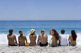 Group of teenagers (17-19) sitting in line on beach, looking at horizon over sea, rear view