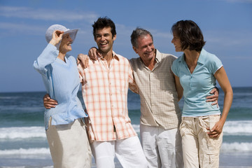 Two couples standing on beach, smiling, front view, portrait