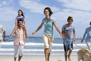 Multi-generational family walking dog on beach, girl (6-8) on father's shoulders, smiling