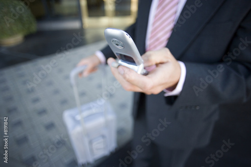 Businessman standing in lobby with luggage, using mobile phone, mid-section (differential focus)