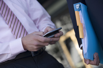 Businessman using personal electronic organiser, second man carrying file, close-up, mid-section