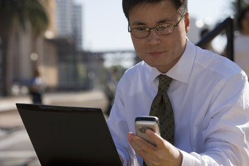 Businessman in spectacles using laptop and mobile phone, outdoors, side view