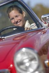 Woman driving red convertible car, smiling, front view, portrait (tilt)