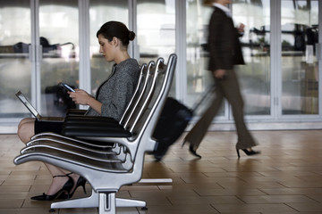 Businesswoman sitting in waiting area, using laptop and electronic organiser, profile